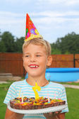 Boy with fruit pie, happy birthday party seven years — Stock Photo