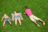 Familia con niño descansando sobre el pasto, vista desde arriba — Foto de Stock