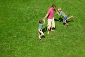 Two boys play with the adult a lawn. The top view. — Stock Photo