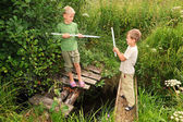 Two boys with sticks battling for fun on bridges over stream — Stock Photo