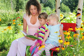Young woman reads the book to two little girls in garden — Foto de Stock