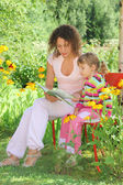 Young woman reads the book to little girl in garden — Stock Photo