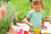 Smiling little girl plays cook in garden — Stock Photo
