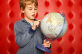 Boy pointing finger on globe. Portrait on red — Stock Photo