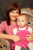 Mother and daughter on her lap sitting in armchair. Interior in — Stock Photo