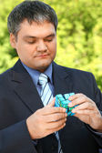 Businessman keeps in hand cube outdoor in summer — Stock Photo