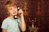 Ritratto di ragazzo in maglietta, parlando con un vecchio telefono contro il muro — Foto Stock