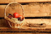 Rural still life. Basket of grapes and apples, and bast shoes on — Stock Photo
