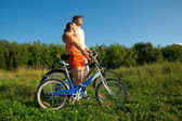 The girl and the man with bicycles embrace each other. — Stock Photo