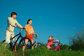 Family from three persons on bicycles. Parents look at a daughte — Stock Photo