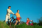Ouders met de dochter op de fiets, in de zomer 's avonds. — Stockfoto