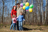 Ouders met de dochter en de zoon lopen in park met ballonnen — Stockfoto