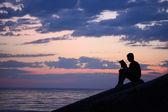 Silhouette guy sitting on breakwater in evening near sea, reads — Stock Photo