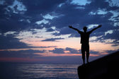 Silhouette guy placed hands in sides on breakwater in evening ne — Stock Photo