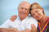 Smiling elderly married couple on veranda near seacoast, concern — Stock Photo