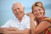 Smiling elderly married couple on veranda near seacoast — Stock Photo