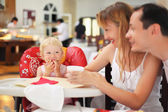 Happy family with blond little girl eating bread — Stock Photo