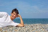 Tiener jongen in wit t-shirt liggend op steenachtige zeekust — Stockfoto