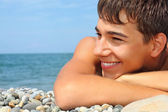 Teenager boy lying on stony seacoast, looking afar — Stock Photo