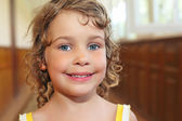 Pretty smiling little girl with curly hair in corridor — Stock Photo