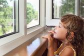 Bardzo uśmiechnięta dziewczynka na balkonie, wyglądają z okna — Zdjęcie stockowe