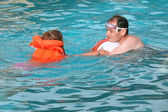 Young man and little girl in lifejacket bathing in pool on reso — Stock Photo