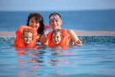 Two little girls bathing in lifejackets with parents in pool on — Stock Photo