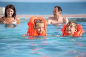Two little girls bathing in life jackets with parents in pool on — Stock Photo