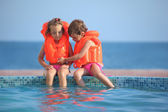 Two little girls in lifejackets sitting on ledge pool on resort — Stock Photo