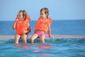 Two little girls in lifejackets sitting on ledge pool on resort, — Stock Photo