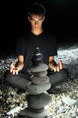 Teenager boy meditating near pyramid from pebble on stony seacoa — Stock Photo