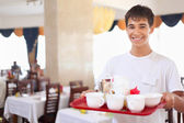 Young smiling affable waiter keeps tray with dishes at restauran — Stock Photo