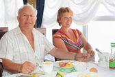 Smiling elderly married couple having breakfast at restaurant ne — Stock Photo