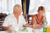 Lachende bejaarde echtpaar ontbijten in het restaurant ne — Stockfoto