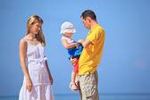 Lycklig familj med liten flicka i vit hatt mot havet — Stockfoto