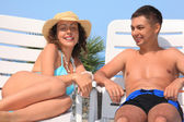 Jonge vrouw en man liggend op chaise lounges open-air glimlachen — Stockfoto