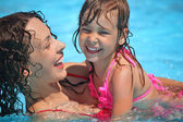 Smiling beautiful woman and little girl bathes in pool — Stock Photo