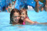 Smiling beautiful woman and little girl bathes in pool in aquapa — Stock Photo
