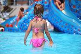 Little girl standing in pool in aquapark, standing back — Stock Photo