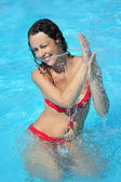 Smiling beautiful woman bathes in pool under water splashes — Stock Photo