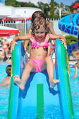 Pretty little girl goes down on hill in aquapark of an entertain — Stock Photo