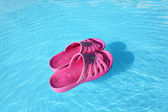 Beach slippers swimming on water surface in pool — Stock Photo