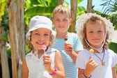 Niños sonrientes tres juntos comen chupa-chups en el parque — Foto de Stock