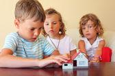 Bambini casa tre insieme guardando al modello di permanente ta — Foto Stock