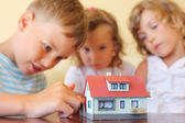 Children three together looking at model of house standing on ta — Fotografia Stock