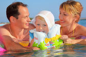 Happy family with little girl in white hat and lifejacket bathin — Stok fotoğraf