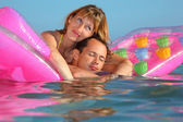Young man and nice women lying on an inflatable mattress in pool — Stock Photo