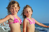 Two pretty little girls on beach near sea, placed hands in sides — Stock Photo