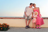 Familia feliz con pequeños sentados en banco en resort — Foto de Stock