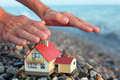Model of house with garage on stony beach in evening, Man's hand — Stock Photo